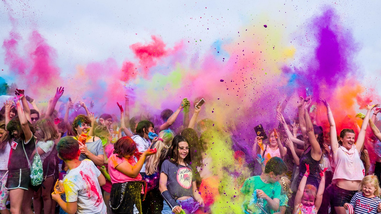 Colour Run event with participants throwing colourful paint in air